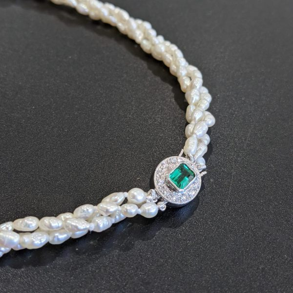 emerald and diamond clasp with a multi strand of pearls necklace
